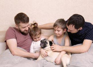 Male gay couple with children resting in bed at home