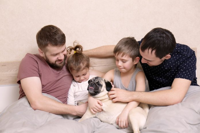 Male gay couple with children resting